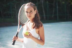 Una mujer bonita vistiendo una cancha de tenis de ropa deportiva en la cancha foto