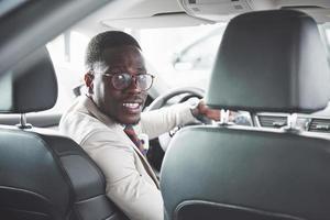 joven empresario negro prueba de conducción coche nuevo. rico hombre afroamericano foto
