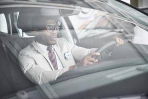Vista frontal del apuesto hombre de negocios serio elegante africano conduce un coche foto