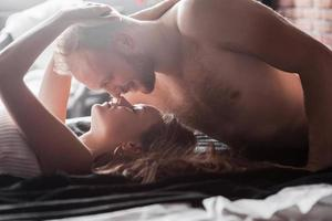 Attractive young lovers have couples playing together in bed, wearing sexy lingerie in a hotel room. photo