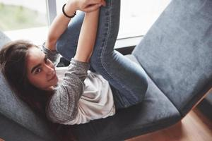 Beautiful young girl spends her time in the recreation area. She sits and has fun in the sofa chair in the form of a hexagon with pillows near the window photo