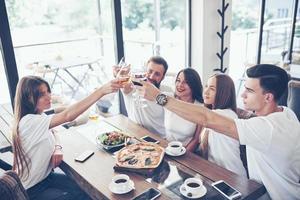 amigos se reunieron por mesa con deliciosa comida con copas de vino tinto para celebrar una ocasión especial foto