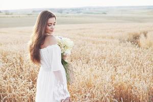 Hermosa chica en vestido blanco corriendo en el campo de trigo de otoño al atardecer foto