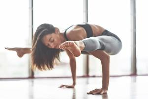 A beautiful young brunette girl performs various yoga stretches. photo