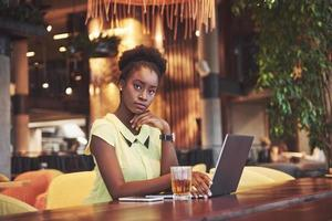 Beautiful young woman sitting in a cafe and working on a laptop photo