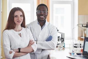 Los laboratorios de laboratorio realizan experimentos en un laboratorio químico en matraces transparentes. fórmulas de salida foto