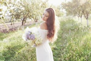 Beautiful young woman wearing elegant white dress and enjoying beautiful sunny afternoon in a summer garden photo