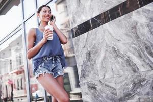 Retrato de mujer joven inconformista con estilo caminando en la calle, vistiendo un lindo atuendo de moda, bebiendo café con leche caliente y sonriendo foto