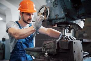 Portrait of a young worker in a hard hat at a large metalworking plant. The engineer serves the machines and manufactures parts for gas equipment photo