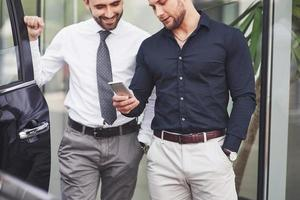 Two happy, confident young businessmen standing by the office photo