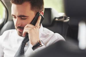 un empresario que envía un mensaje a un teléfono inteligente y se dirige al asiento trasero del automóvil. foto