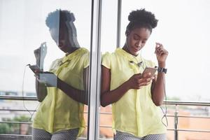 Portrait of attractive young black woman with mobile phone and headphones while listening to music photo