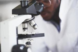 The scientist works with a microscope in a laboratory conducting experiments and formulas. photo