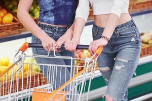 Busy and beautiful women are shopping at a supermarket with a cart. photo