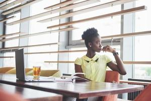 Young African American girl with dark curly hair pensive in a cafe. photo