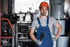 retrato de un joven trabajador con un casco en una gran planta metalúrgica. el ingeniero atiende las máquinas y fabrica piezas para equipos de gas foto