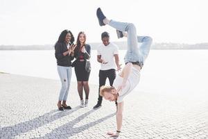 Street artist breakdancing outdoors. Surprised friends applaud photo