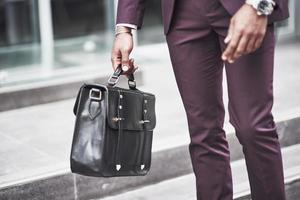 Young businessman with a briefcase near a beautiful office. Business meeting. photo