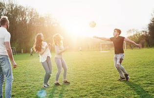 A group of friends in casual outfit play soccer in the open air. People have fun and have fun. Active rest and scenic sunset. photo