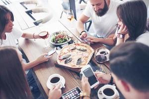 Sabrosa pizza en la mesa, con un grupo de jóvenes sonrientes descansando en el pub foto