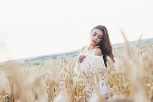 hermosa chica en un campo de trigo con un vestido blanco, una imagen perfecta en el estilo de vida foto