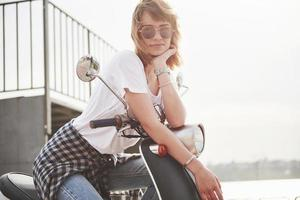 Portrait of a beautiful girl hipster sitting on a black retro scooter, smiling posing and enjoy the warm spring sunshine. photo