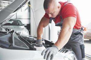 mecánico de automóviles trabajando en garaje. servicio de reparación. foto