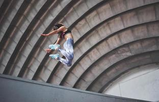 Woman doing parkour in the city on a sunny day photo