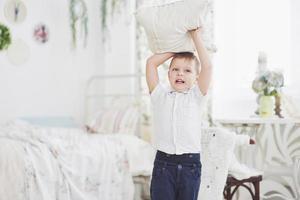niño con camisa blanca con almohada. pelea de almohadas foto