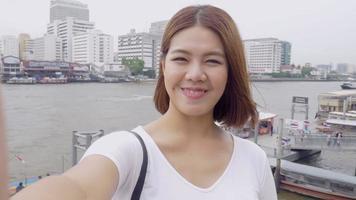Sonrisa hermosa mujer asiática tomando autorretratos en un teléfono inteligente. video