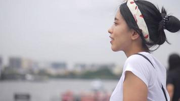 mujer asiática joven que mira el río de la vista en la ciudad. video