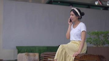 Asian woman sitting chair talking on phone smiling and happiness. video