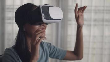 Asian woman playing game and watching movie in vr glasses. Happy asian girl using 3D virtual reality headset at home. video