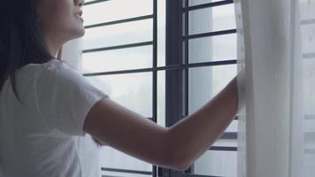 retrato jovem mulher asiática abrindo as cortinas na sala em casa, olhando pela janela e estendendo-se no período de férias da manhã. video
