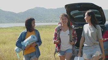 Asian women helps to hold backpacks and ice coolers with friends camping in nature having a summer traveling. video