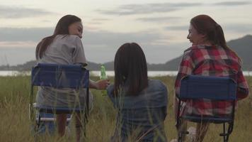 Asian woman sitting on a chair with friends camping in nature having fun together drinking beer and clinking glasses. video