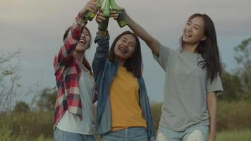 Asian woman happy friends camping in nature having fun together drinking beer and clinking glasses. video