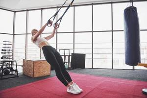Women doing push ups training arms with trx fitness straps in the gym Concept workout healthy lifestyle sport photo