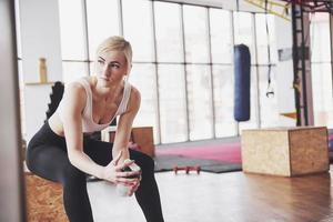 Photo of attractive fitness woman in gym holding bottle of water