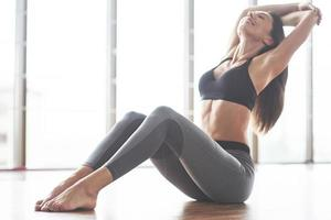 A beautiful yoga woman practicing in a spacious light gym photo