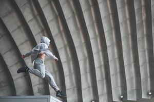 The man outdoors practices parkour, extreme acrobatics. photo