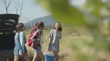 les femmes asiatiques aident à tenir des sacs à dos et des glacières avec des amis campant dans la nature en voyageant l'été. video