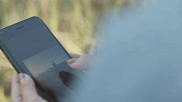 Junge mit einem Smartphone, der das Foto überprüft, nachdem er ein Foto mit Freunden gemacht hat. video