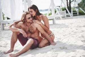 una pareja romántica en la playa en traje de baño, hermosos jóvenes sexy foto