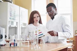 Los científicos trabajan en estrecha colaboración con el microscopio en el laboratorio mediante la realización de experimentos y análisis. foto