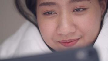 Asian woman on the bedroom using a tablet browsing online social media sharing lifestyle. video