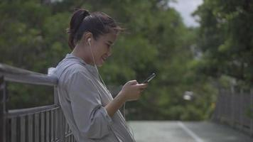Asian woman fitness runner standing using mobile phone listening music at a public park. video