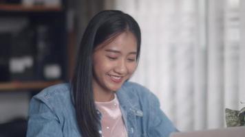 Diseño creativo de mujer asiática usando laptop en la oficina en casa. video