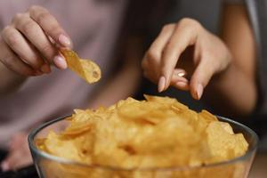 women couch watching tv eating chips close up photo
