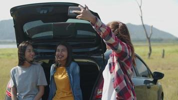 Asian woman selfie-taking photo on the mobile phone with friends camping in nature having a summer traveling. video